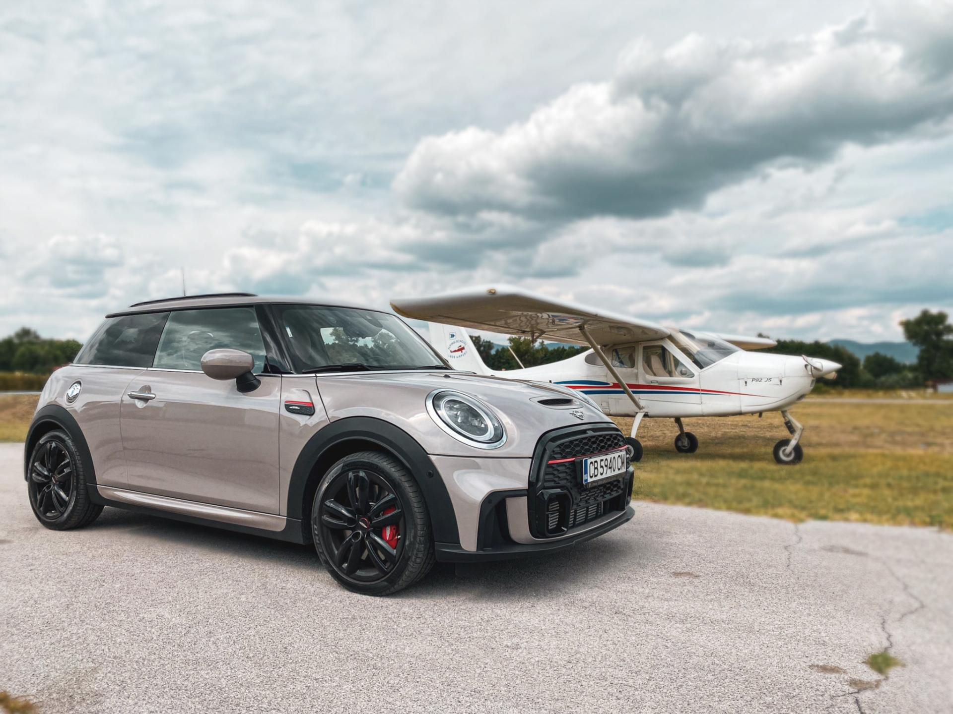 MINI JCW LCI and a small plane. at the back