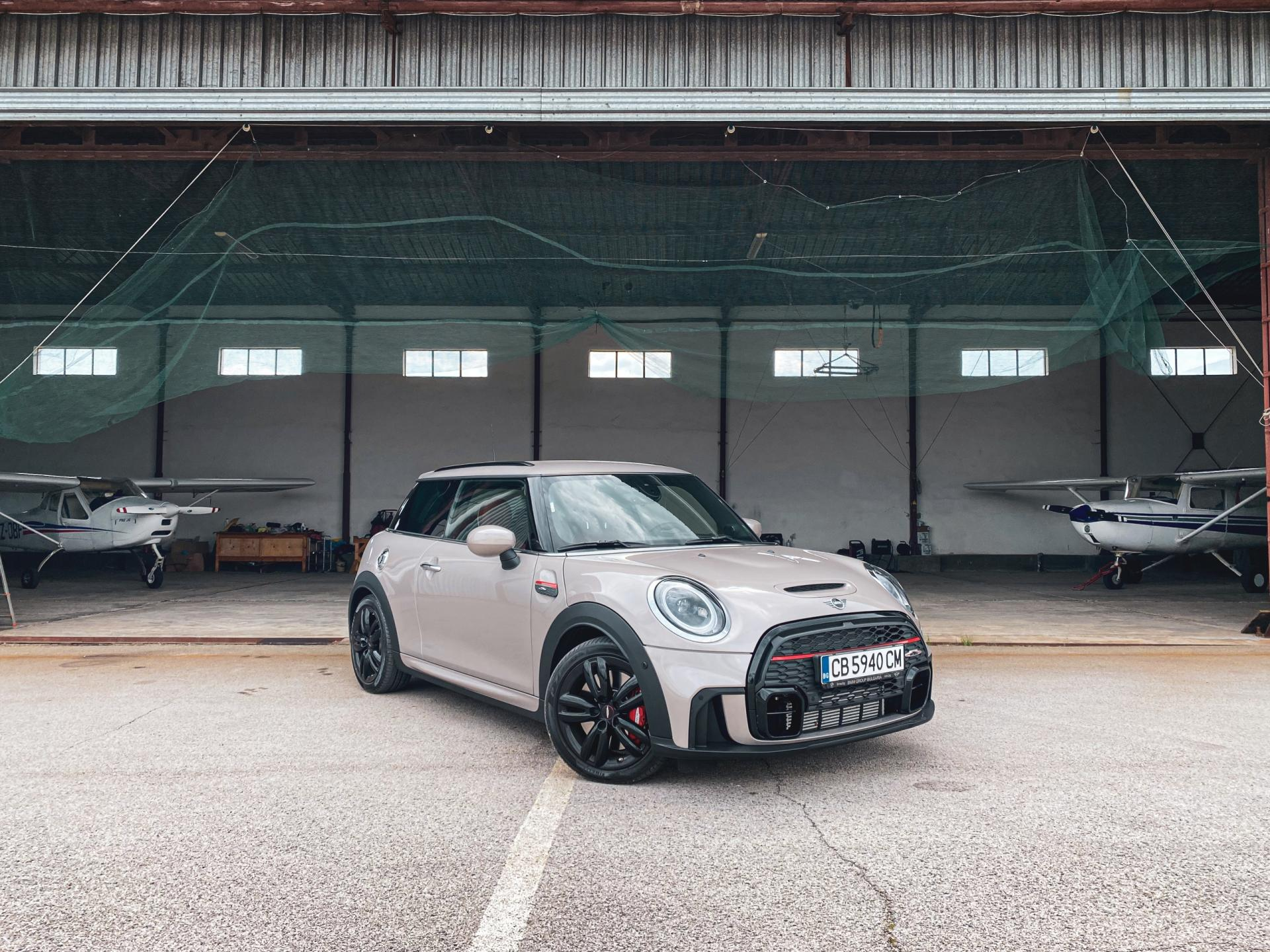 MINI JCW LCI infront a plane hanger, surrounded by two planes